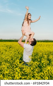 Young man with child having fun in a blooming yellow field at sunset