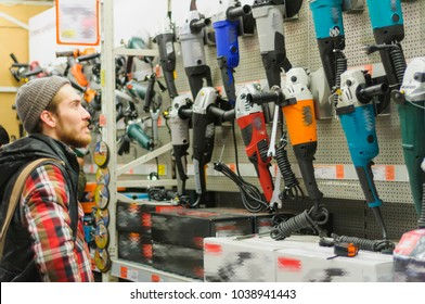 A young man chooses angle grinder in the hardware store