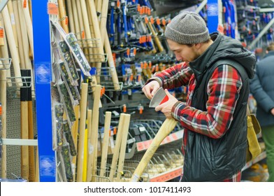 A young man chooses axe in the hardware store