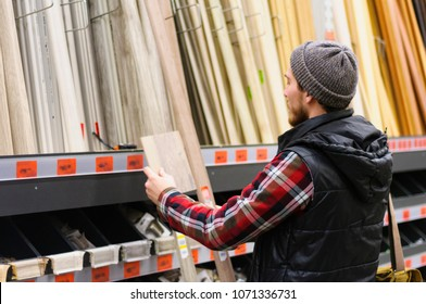 A young man chooses baseboard in the hardware store