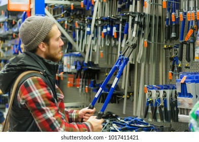 A young man chooses bolt cutter in the hardware store