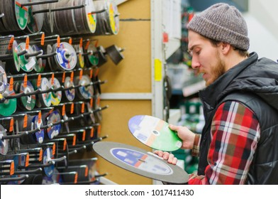 A young man chooses discs for angle grinder in the hardware store