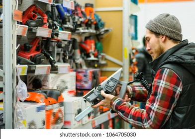 A young man chooses electric jack-plane in the hardware store