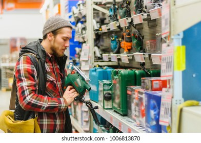 A young man chooses electric jig saw in the hardware store