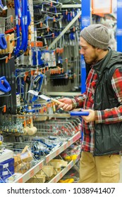 A young man chooses hand saws in the hardware store