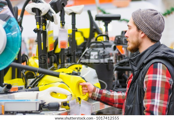 A young man chooses a high pressure washer in the hardware store