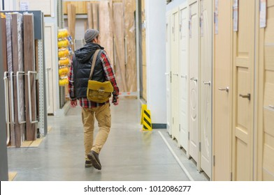 A young man chooses interroom door in the hardware store