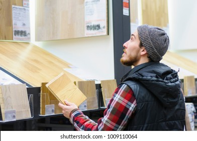 A young man chooses laminate flooring in the hardware store