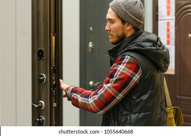 A young man chooses metal front door in the hardware store