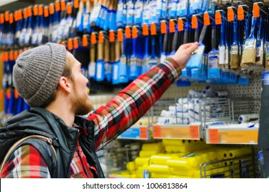 A young man chooses paintbrush in the hardware store