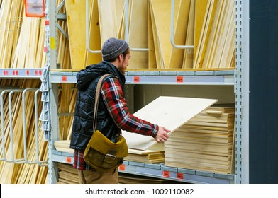 A young man chooses plywood in the hardware store
