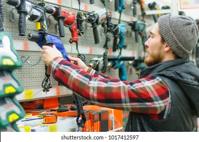 A young man chooses powerful drill in the hardware store