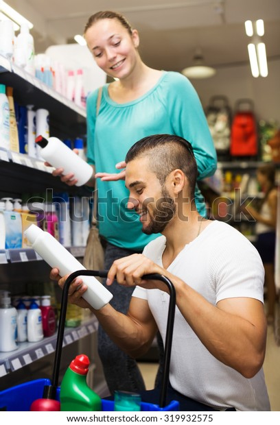 Young man chooses shampoo in supermarket