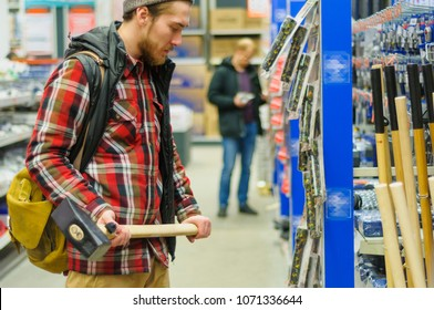 A young man chooses sledgehammer in the hardware store