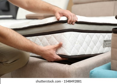 Young man choosing new orthopedic mattress in store, closeup