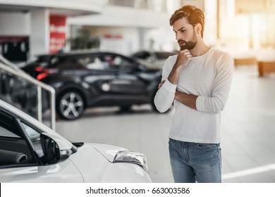 Young man is choosing a new vehicle in car dealership.