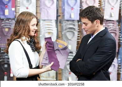 Young man choosing shirt and necktie during apparel shopping at clothing store