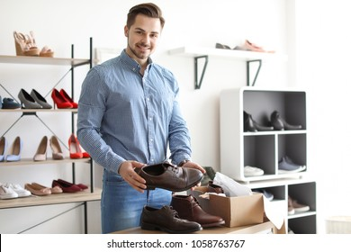 Young man choosing shoes in store