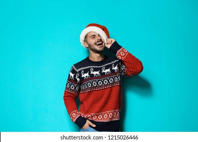 Young man in Christmas sweater and hat on color background