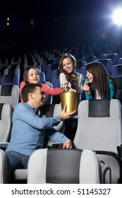 The young man at cinema gives girls pop-corn