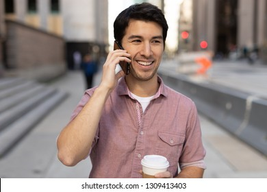 Young man in city walking talking on cell phone