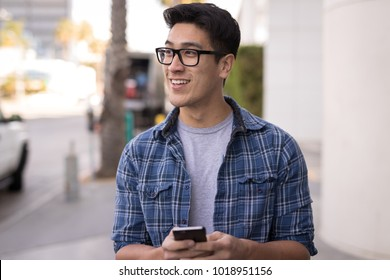 Young man in city walking texting cell phone
