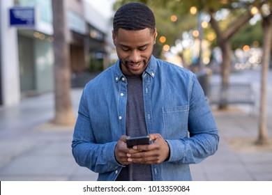 Young man in city walking using cellphone