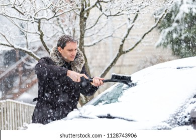 Young man cleaning car windshield from snow, ice with brush and scraper tool during snowfall during winter snowing snowflakes falling