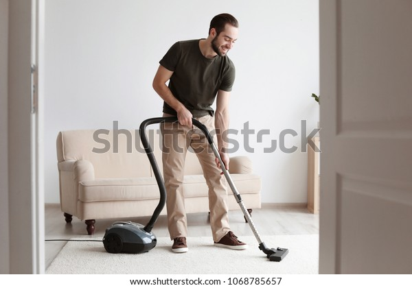 Young man cleaning carpet with vacuum in living room
