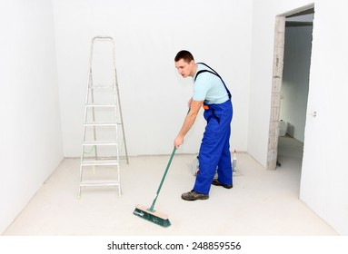Young man cleaning floor with brush after repair
