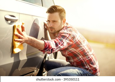 Young man cleaning his car outdoors.Man with a microfiber wipe the car polishing