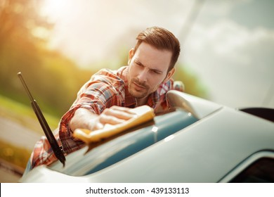 Young man cleaning his car outdoors.He is polishing rear windshield.