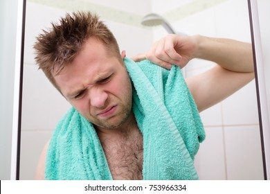 Young man cleaning his ear while taking a shower and standing under flowing water