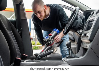 Young man cleaning the interior of a car using a  handheld portable vacuum cleaner.