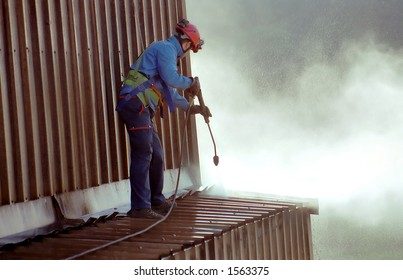 Young man, cleaning the roof of an ironworks.