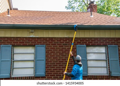 Young man cleaning the soffit of a house with a brush on a long pole. The house has blue shutters and is one story high
