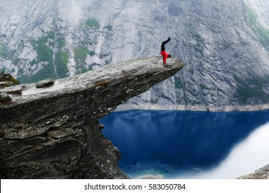 Young man climber in red jacket making intrepid handstand at the edge of famous Troltunga cliff over blue water of Ringedalsvatnet lake in canyon. Norway, summer scenery. Wanderlust concept.