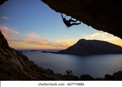 Young man climbing along ceiling of cave at sunset, Kalymnos island, Greece. Beautiful evening view of Telendos island in background.