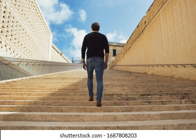 A young man climbing up along large endless stair alone