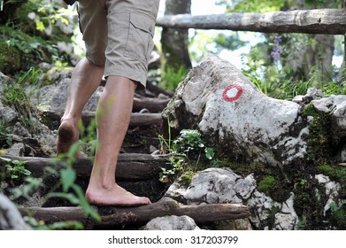 Young man climbing barefoot, closeup with trail mark in the background.