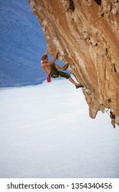 Young man climbing challenging route on overhanging cliff