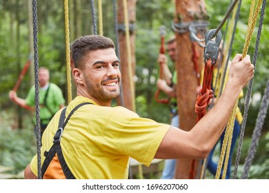 Young man in climbing forest or high ropes course at teambuilding event