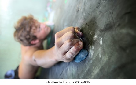 Young man climbing indoor wall. Focus on a fingers