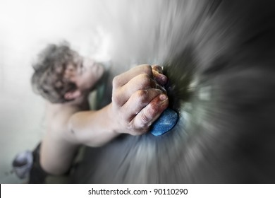 Young man climbing indoor wall. Focus on a fingers. Motion blurred wall around hand