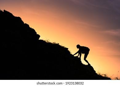 Young man climbing up mountain