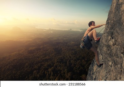 Young man climbing natural rocky wall at sunrise