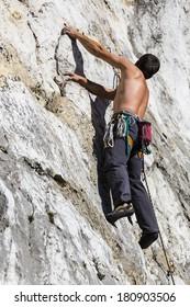 A young man climbing on a limestone wall toward the peak