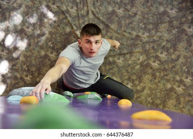 Young Man Climbing On Practice Wall In Gym And Looking Up
