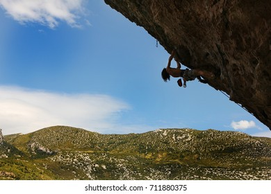 Young man climbing on the rock wall against a blue sky and mountain landscape.