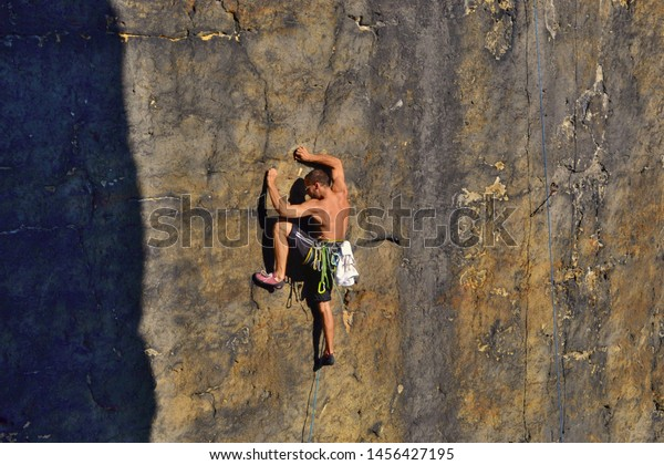 Young man is climbing on the sandstone rock in Sachsen Switzerland. Beautiful autumn day in Germany.